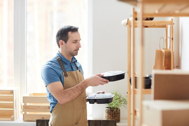 Homem maduro de avental empilhando embalagens plásticas nas prateleiras enquanto trabalhava em um serviço de entrega de comida