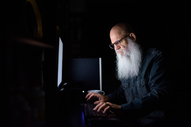 Homem maduro de barba careca estressado fazendo hora extra em casa no escuro