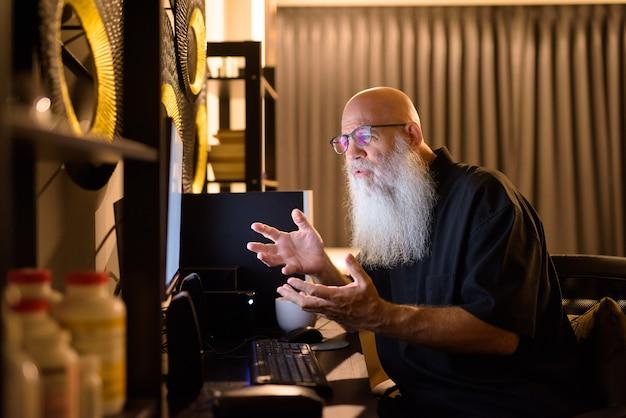 Homem maduro de barba careca fazendo videochamadas no trabalho de casa tarde da noite