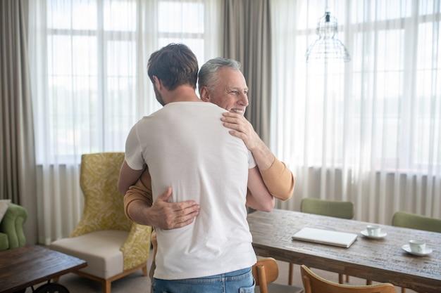 Homem maduro de cabelos grisalhos abraçando sua sona e parecendo feliz
