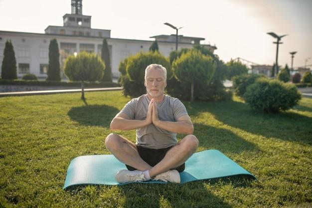Homem maduro de cabelos grisalhos meditando com os olhos fechados e as mãos em namaste