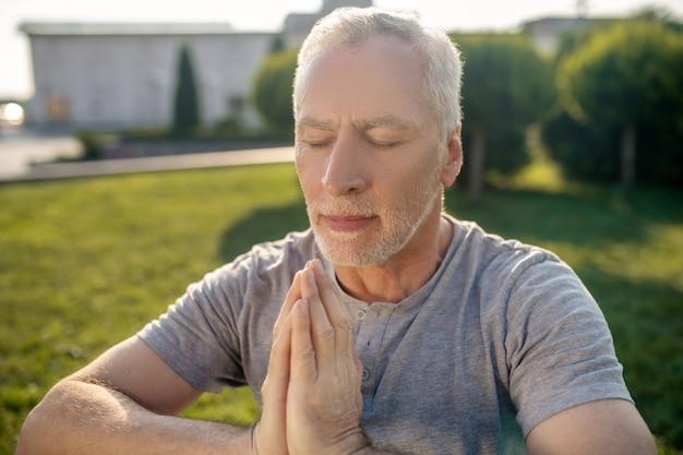 Homem maduro de cabelos grisalhos meditando do lado de fora, mãos namastê