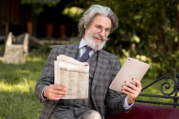 Homem maduro de frente segurando jornal e tablet