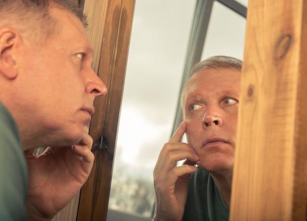 Homem maduro de meia-idade, olhando no reflexo do espelho e observando as rugas perto dos olhos.