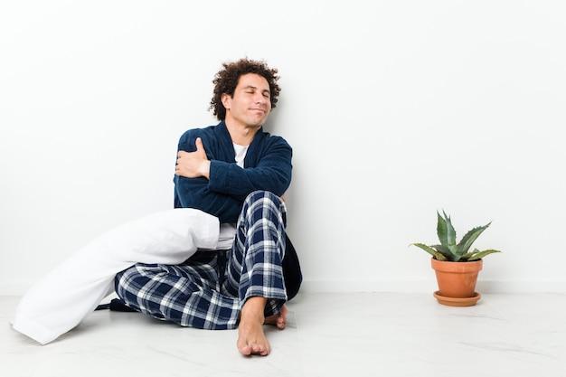 Homem maduro de pijama sentado no chão da casa abraços, sorrindo despreocupado e feliz.