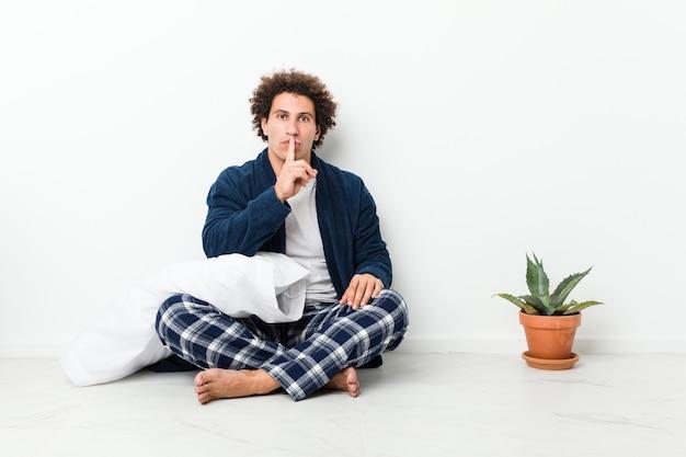Homem maduro de pijama, sentado no chão da casa, escondendo um segredo ou pedindo silêncio.
