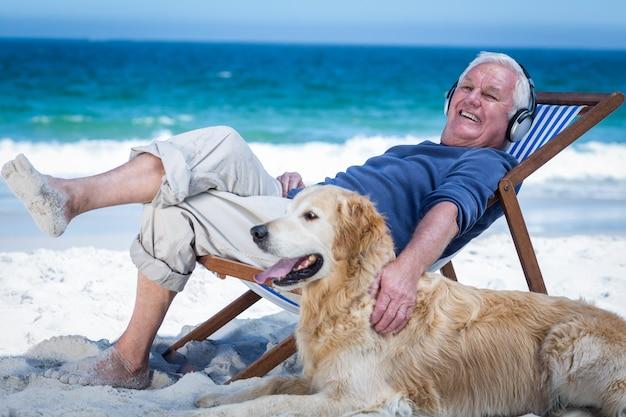 Homem maduro, descansando em uma espreguiçadeira, ouvindo música, acariciando seu cachorro