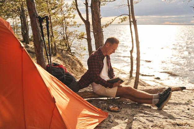 Homem maduro e atlético vai acampar na floresta acima da costa do mar e tomar o café da manhã enquanto lê o livro