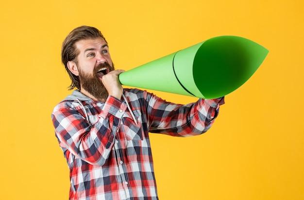 Homem maduro e bonito com camisa quadriculada fala no alto-falante de papel, anúncio.