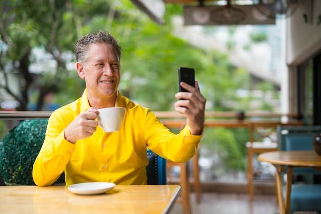 Homem maduro e bonito sentado em uma cafeteria enquanto tira uma selfie