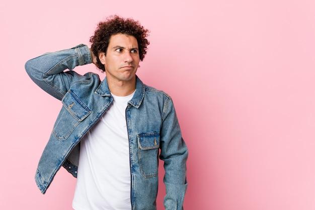 Homem maduro e cacheado usando uma jaqueta jeans contra a parede rosa tocando a nuca, pensando e fazendo uma escolha
