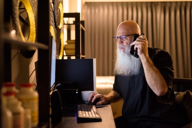 Homem maduro e careca barbudo falando ao telefone enquanto trabalhava horas extras em casa tarde da noite