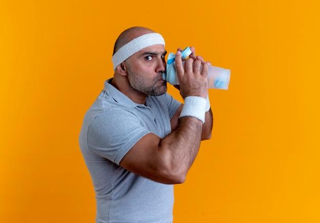 Homem maduro e desportivo com fita na cabeça, bebendo água após o treino, olhando para a frente com uma cara séria em pé sobre a parede laranja