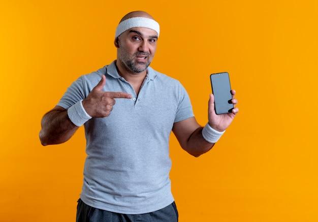Homem maduro e desportivo com uma bandana mostrando o smartphone apontando com o dedo para ele, parecendo confiante em pé sobre a parede laranja