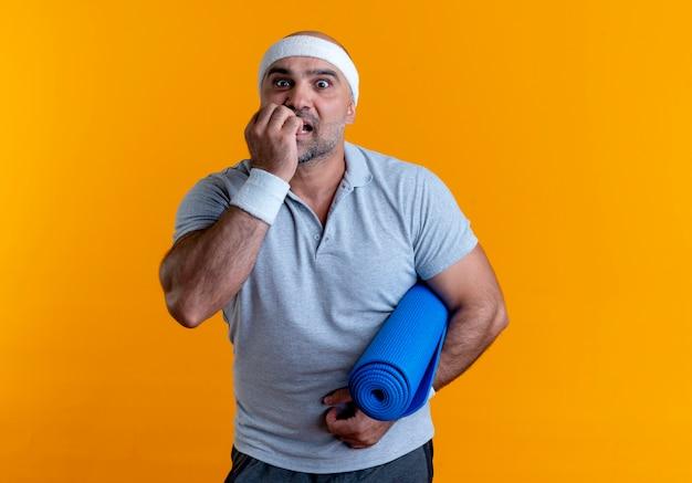 Homem maduro e desportivo com uma bandana segurando um tapete de ioga, estressado e nervoso, em pé sobre uma parede laranja