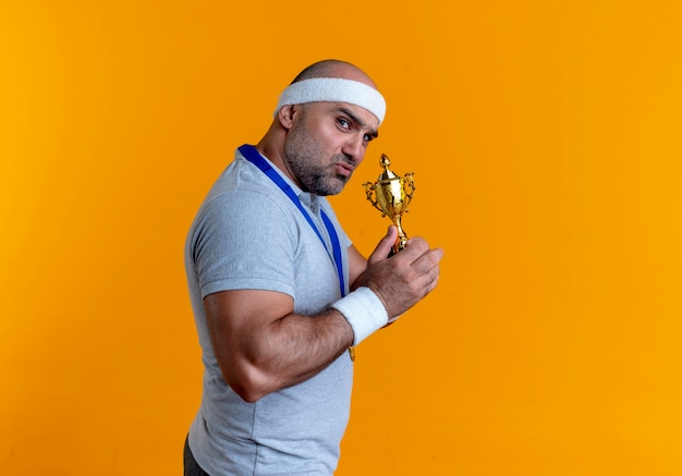 Homem maduro e desportivo com uma faixa na cabeça e uma medalha de ouro no pescoço segurando um troféu olhando para a frente com uma cara séria em pé sobre a parede laranja