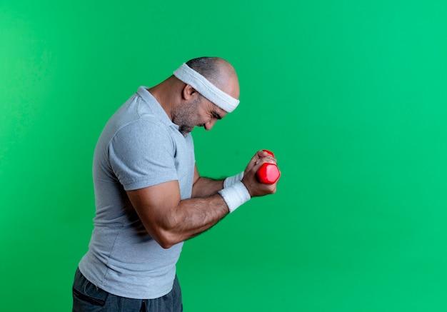 Homem maduro e desportivo com uma faixa na cabeça, malhando com halteres, parecendo tenso e confiante em pé sobre a parede verde 3