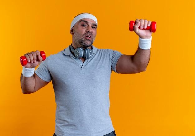 Homem maduro e desportivo com uma faixa na cabeça, malhando com halteres, parecendo tenso e confiante em pé sobre uma parede laranja 3