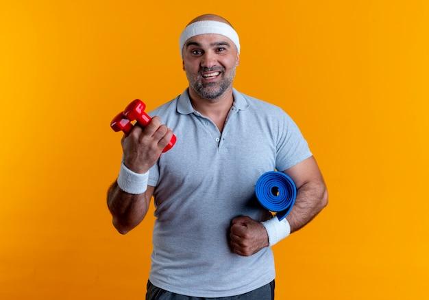 Homem maduro e desportivo com uma faixa na cabeça, segurando dois halteres e um tapete de ioga, olhando para a frente, sorrindo feliz e positivo em pé sobre a parede laranja