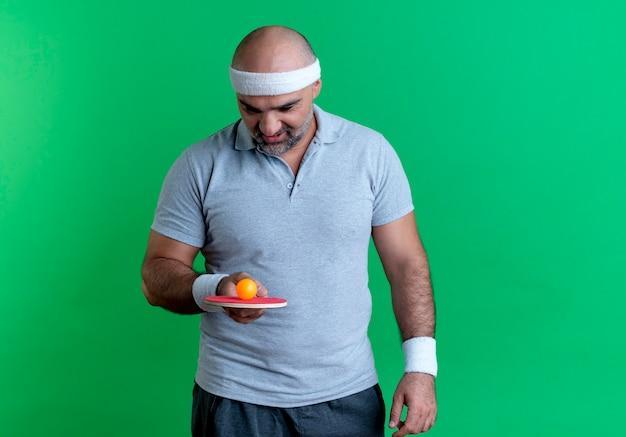 Homem maduro e desportivo com uma faixa na cabeça segurando uma raquete com uma bola de tênis de mesa, olhando para ela com interesse em pé sobre a parede verde