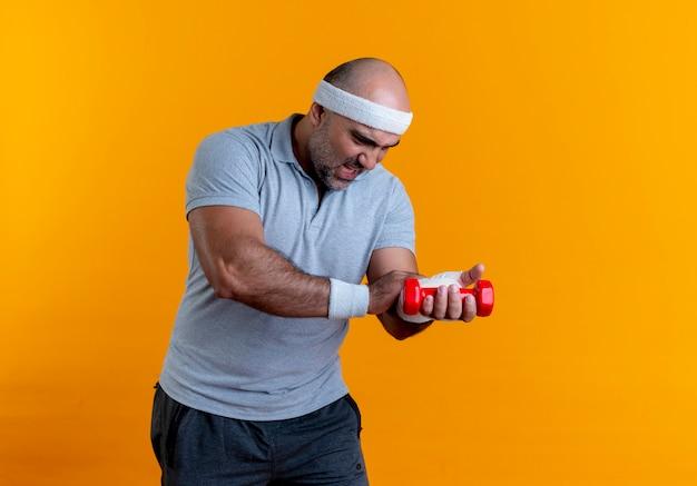 Homem maduro e desportivo com uma faixa na cabeça, tocando a mão enfaixada, parecendo indisposto, sofrendo de dor em pé sobre a parede laranja