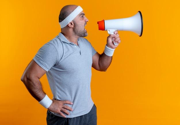 Homem maduro e esportivo com uma bandana gritando para o megafone e uma expressão agressiva em pé sobre a parede laranja