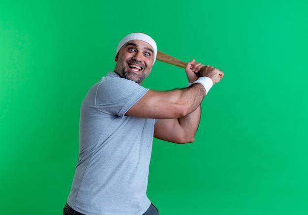 Homem maduro e esportivo com uma faixa na cabeça balançando um taco de beisebol e sorrindo alegremente em pé sobre a parede verde