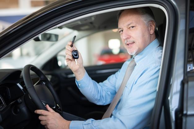 Homem maduro e feliz mostrando a chave de seu carro novo em um salão de uma concessionária