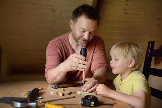 Homem maduro e garotinho fazem um brinquedo de madeira juntos.