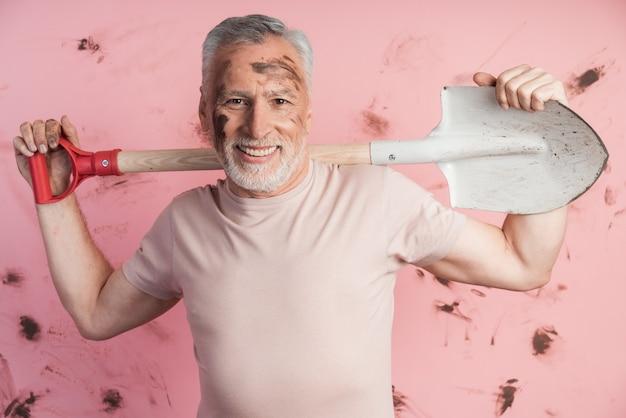 Homem maduro e idoso com uma pá nos ombros em uma parede rosa suja