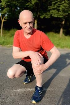 Homem maduro e idoso sentado no parque e tocando seu joelho por causa da dor durante o dia.