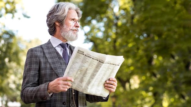 Homem maduro elegante segurando jornal
