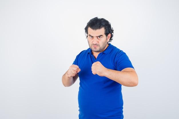 Homem maduro em pose de luta em camiseta azul, calça jeans e parecendo confiante. vista frontal.