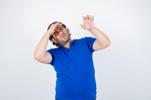 Homem maduro em t-shirt azul, jeans olhando para longe com a mão na cabeça, esticando a mão e olhando com foco, vista frontal.