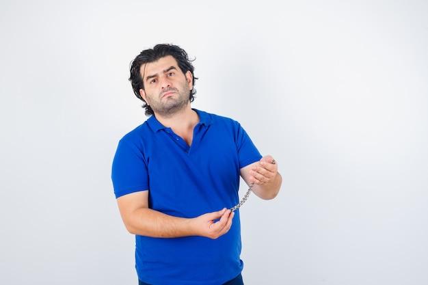 Homem maduro em t-shirt azul, segurando a corrente e olhando perplexo, vista frontal.