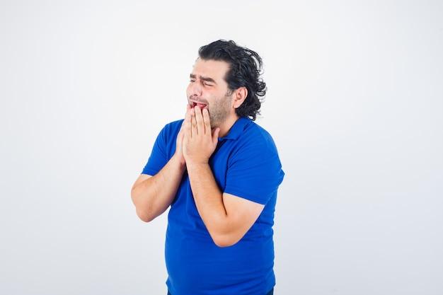 Homem maduro em t-shirt azul, segurando as mãos perto da boca e parecendo triste, vista frontal.