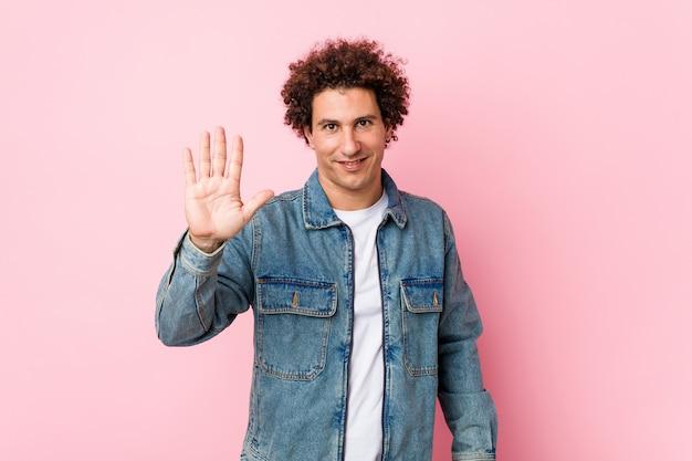 Homem maduro encaracolado, vestindo uma jaqueta jeans contra fundo rosa sorrindo alegre mostrando número cinco com os dedos.