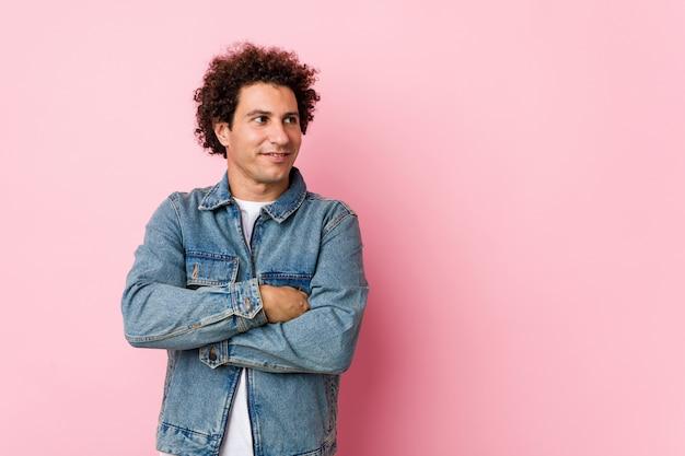 Homem maduro encaracolado, vestindo uma jaqueta jeans contra fundo rosa sorrindo confiante com braços cruzados.