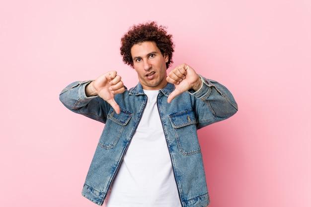 Homem maduro encaracolado, vestindo uma jaqueta jeans contra parede rosa, mostrando o polegar para baixo e expressando aversão.