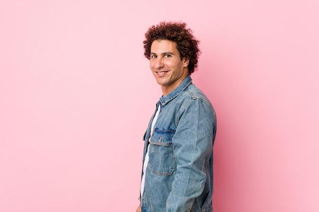 Homem maduro encaracolado, vestindo uma jaqueta jeans contra parede rosa parece de lado sorridente, alegre e agradável.