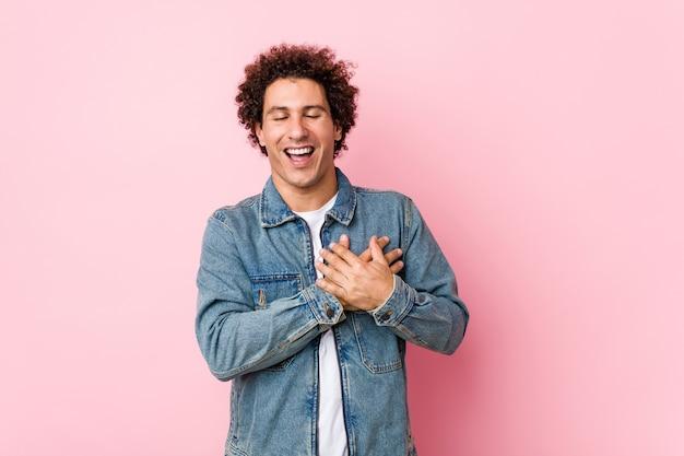 Homem maduro encaracolado vestindo uma jaqueta jeans contra parede rosa rindo mantendo as mãos no coração, o conceito de felicidade.