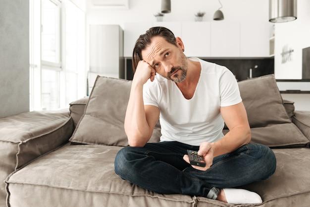 Homem maduro entediado, sentado em um sofá