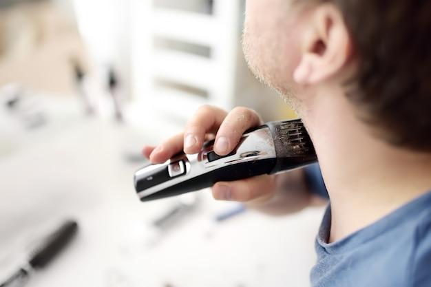 Homem maduro está raspando a barba com um barbeador elétrico em casa