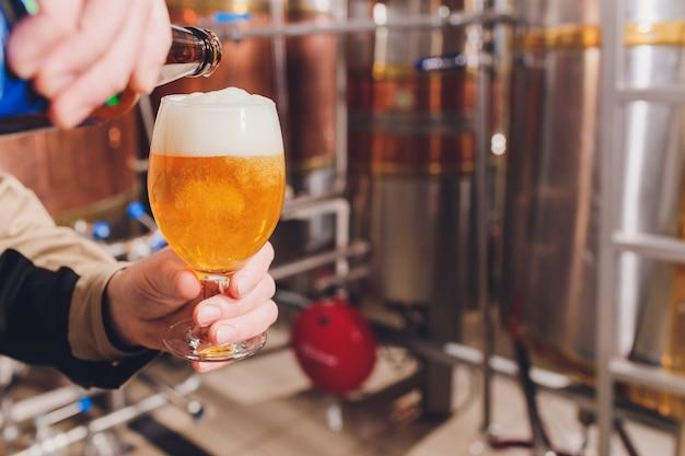 Homem maduro, examinando a qualidade da cerveja artesanal na cervejaria. inspetor trabalhando na fábrica de fabricação de álcool, verificando a cerveja. homem na destilaria, verificação de controle de qualidade de chope.