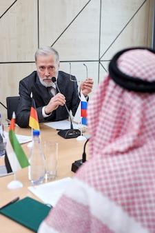 Homem maduro executivo mantém reunião política com o xeque, conversando com ele, retrovisor no homem árabe no manto tradicional vermelho. na sala de reuniões