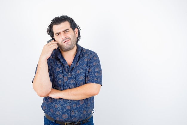 Homem maduro, falando no celular com camisa e parecendo entediado, vista frontal.