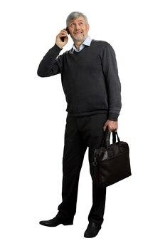 Homem maduro, falando no telefone. homem de cabelo grisalho com telefone olhando para cima em branco. retrato de corpo inteiro.