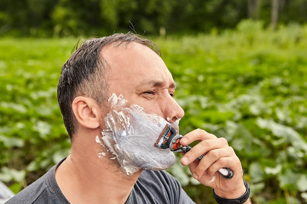 Homem maduro faz a barba ao ar livre usando espuma de barbear e navalha.