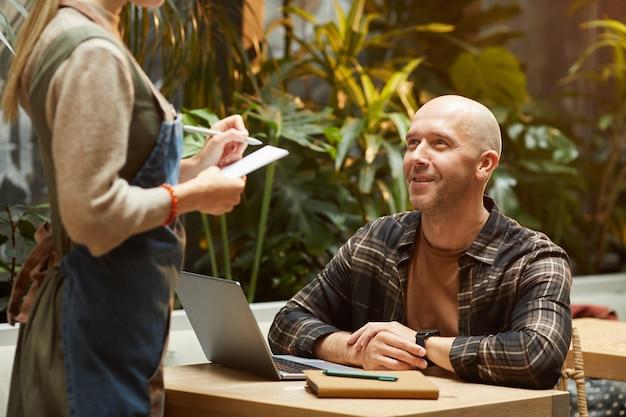 Homem maduro fazendo um pedido para o garçom enquanto está sentado à mesa com um laptop no restaurante