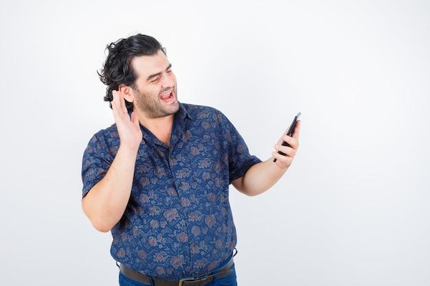 Homem maduro, fazendo videochamada no celular na camisa e parecendo alegre, vista frontal.